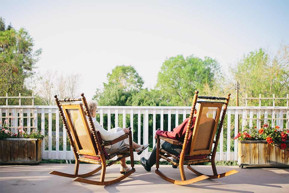 Elderly couple sitting in rocking chairs on the pack porch of a long-term care facility.