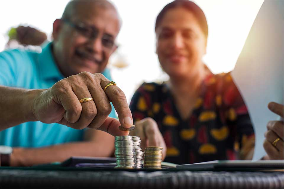 Elderly couple stacking quarters and other loose change.