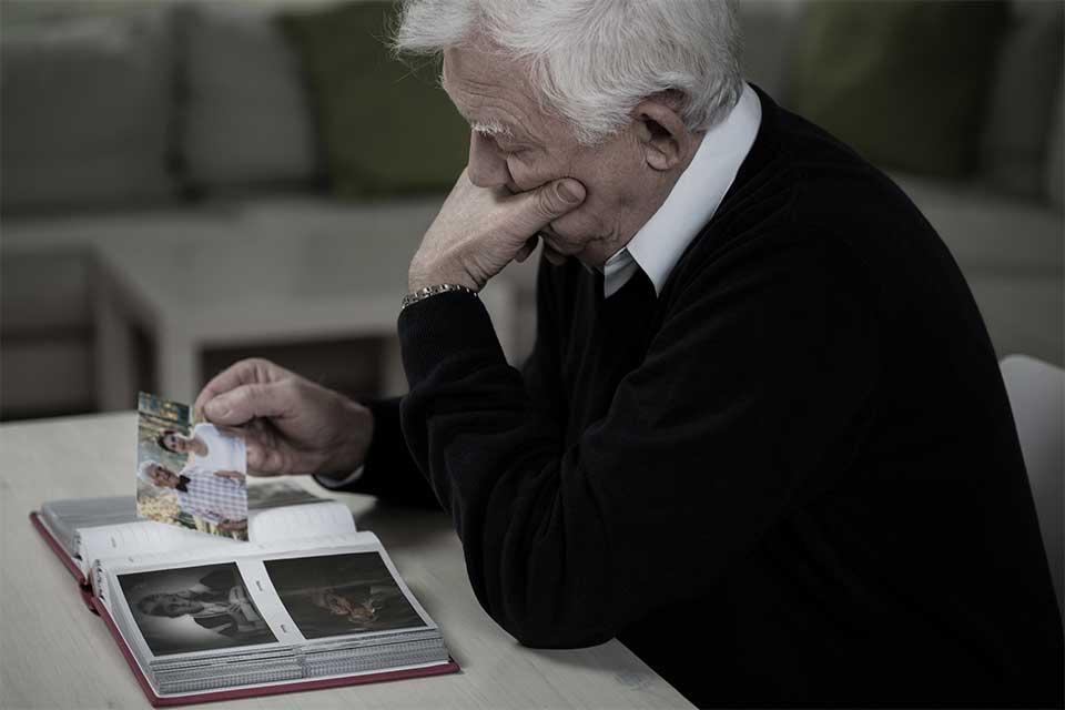 Elderly man suffering from senior isolation looking through a photo album