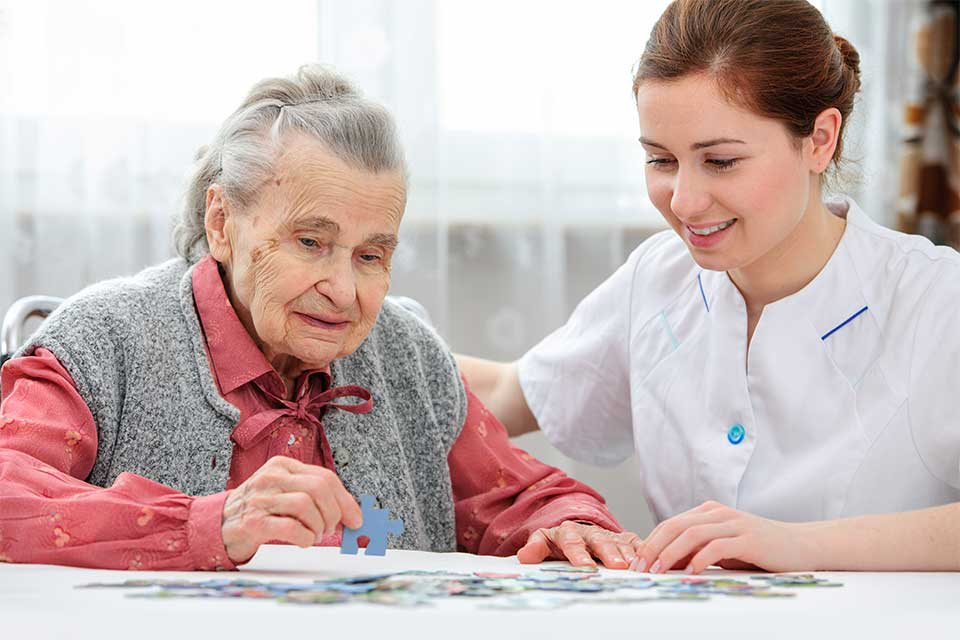 Elderly woman in dementia care putting together a puzzle