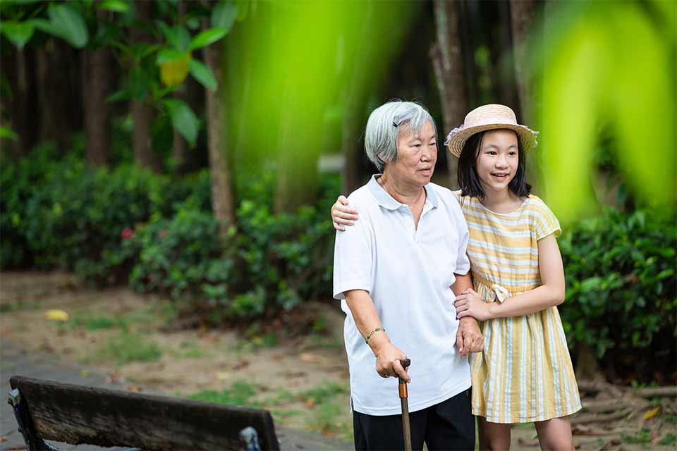 Elderly Asian woman being helped by her granddaughter to walk.