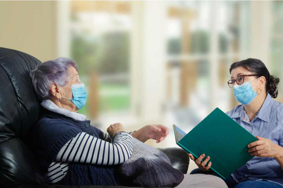 An essential caregiver reading a story to a female senior citizen while they both wear protective face masks.