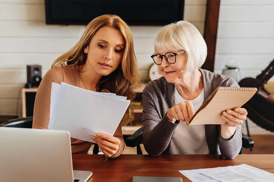Elderly woman receiving savvy financial advice from her daughter.