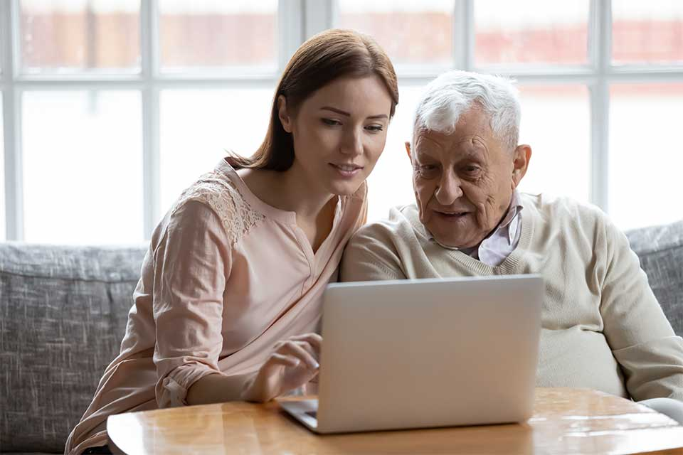 Elderly man and his daughter touring a senior living community on their laptop.