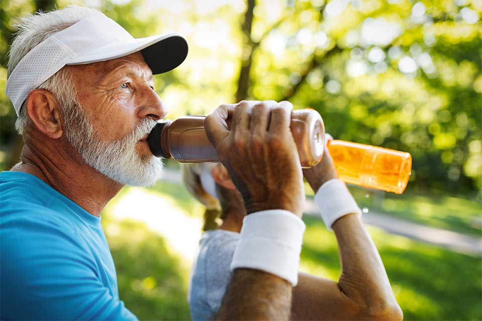 Elderly couple drinking water from water bottles after working out