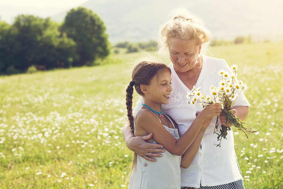 Elderly woman in a field with her granddaughter picking daisies.