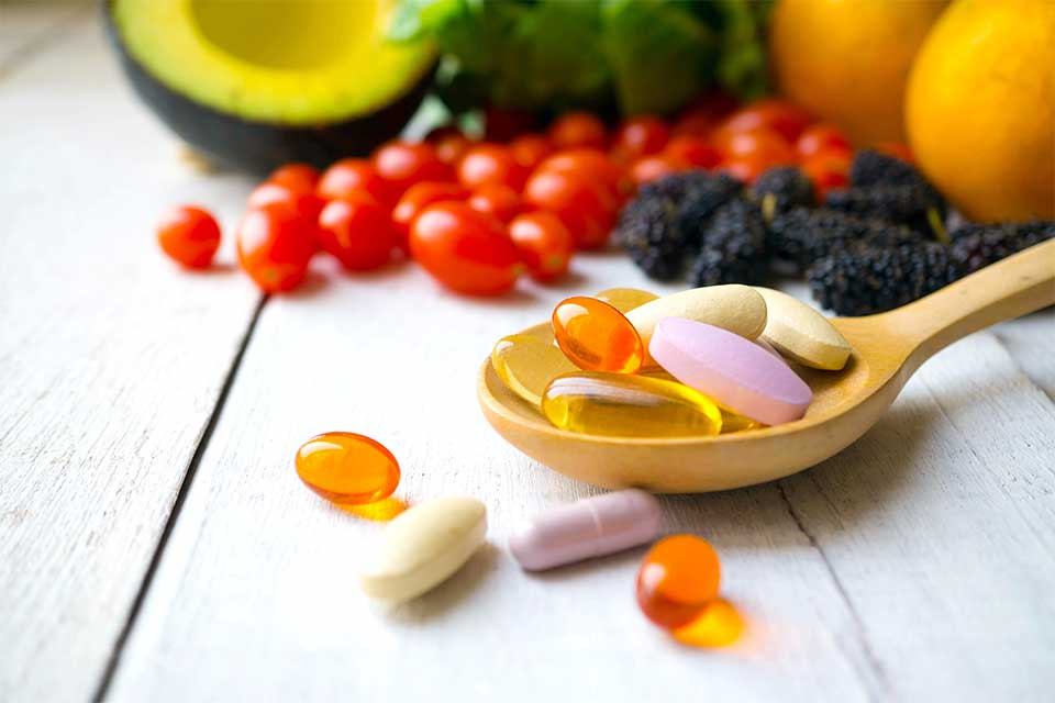 Various vitamins in a wooden spoon surrounded by fresh fruits and vegetables.