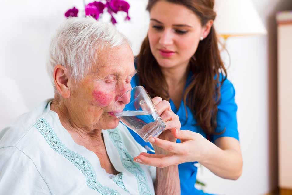 Elderly woman with rosy cheeks receiving assistance from a nurse to drink a glass of water.