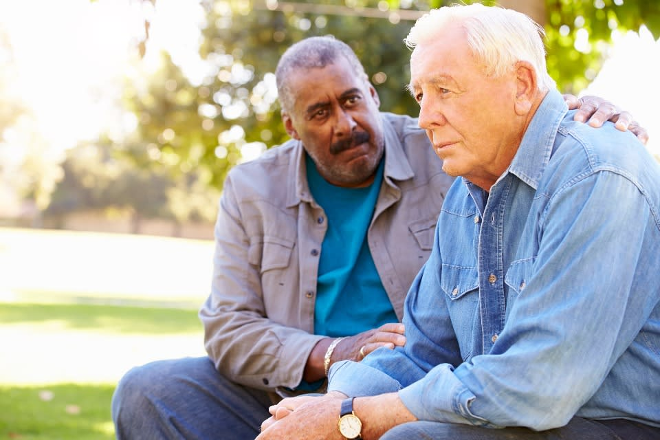 A friend consoles an elderly man whose partner has died.