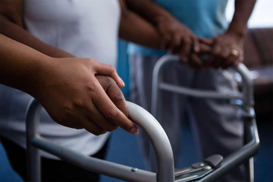 Elderly woman in a nursing home receiving help from a nurse to walk with a walker.