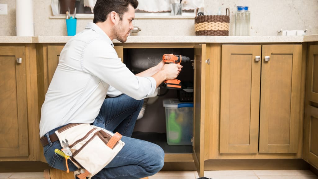 A handyman drilling into a cabinet - a common service on a handyman services list