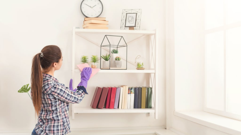 A woman dusts, tackling her Spring Cleaning List Room by Room