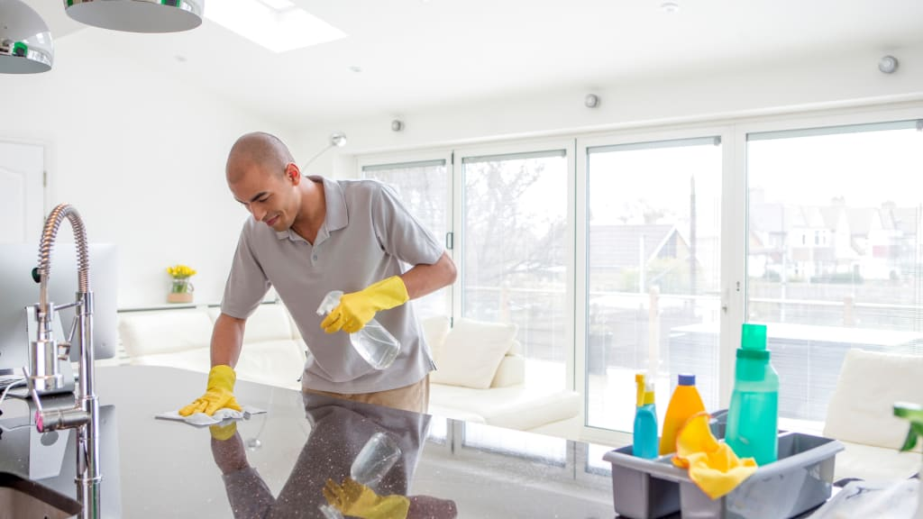 A man cleans a counter while tackling his Spring Cleaning List in the Kitchen