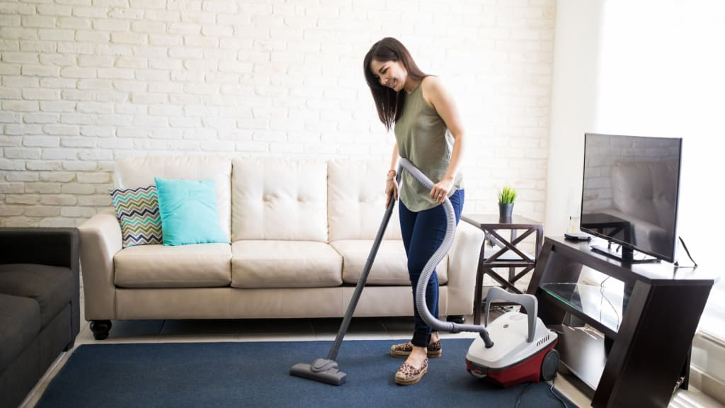 A woman vacuums while tackling her Spring Cleaning List Room by Room