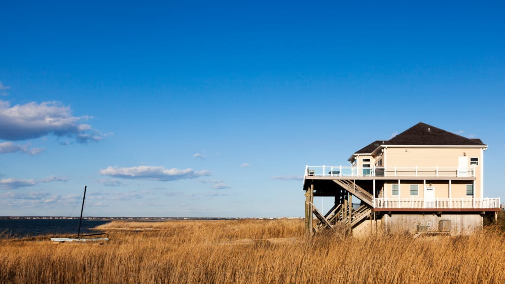 A vacation home in need of some vacation home cleaning sits on a marsh by the ocean