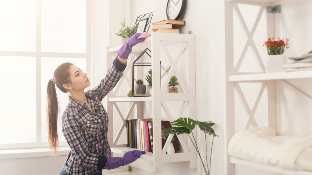A woman dusts a bookshelf while wearing gloves, part of her vacation home cleaning list