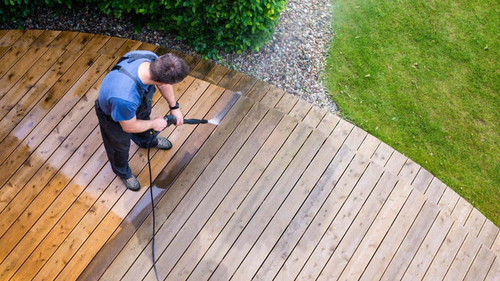 A man power washes a deck as part of vacation home cleaning