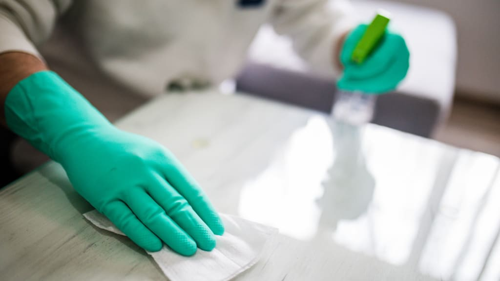 A gloved hand hand wiping down a counter as part of deep house cleaning services