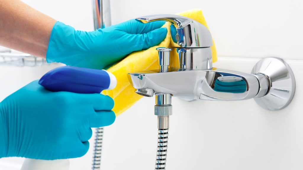 Two gloved hands wiping a bathtub faucet as part of deep house cleaning services.