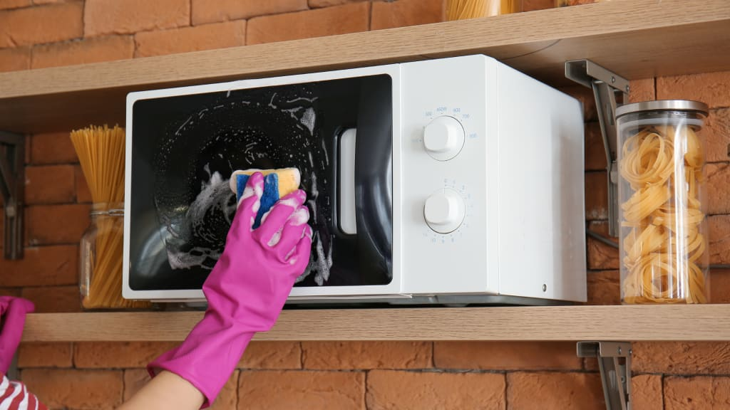A gloved hand uses a sponge to wipe down the outside of a microwave as part of deep house cleaning services.