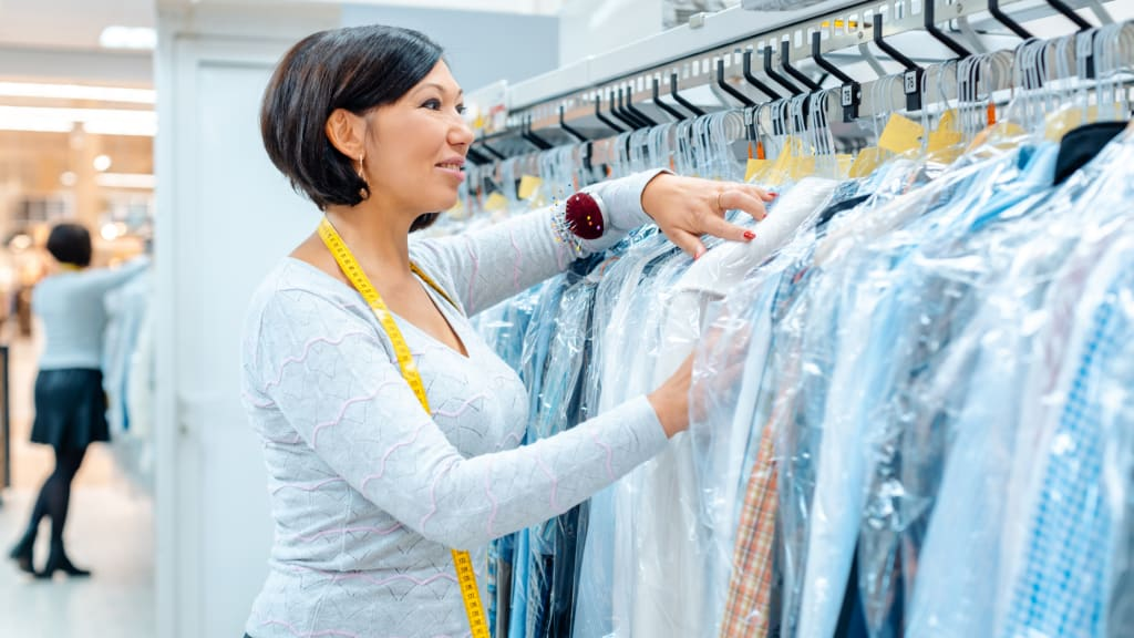 A woman looks over dry cleaning orders, part of personal errand services.