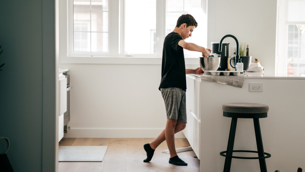 A boy works in a kitchen, one of many age appropriate chores for kids to do