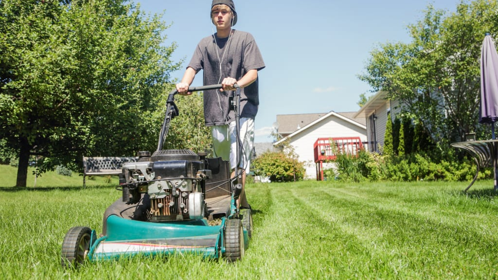 A teenager mows the lawn - one of many age appropriate chores for kids to do