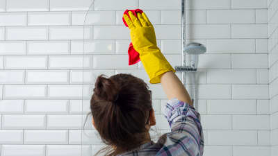 woman cleans, wondering is it safe to hire a cleaning service during covid-19