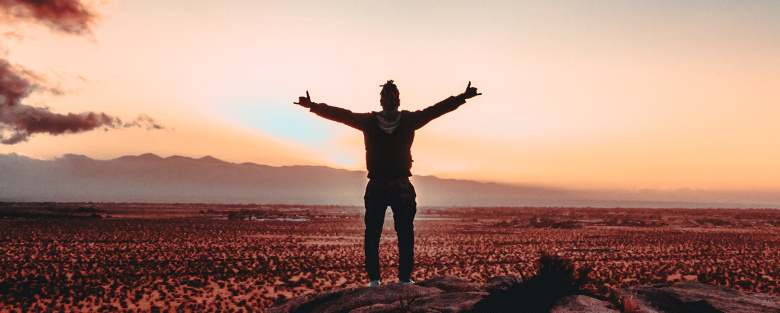 person standing on rock raising both hands for victory