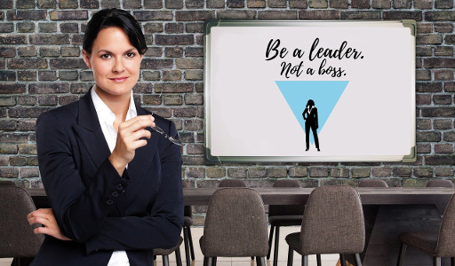 "Woman in Meeting room whiteboard on wall says ""Be a Leader not a Boss"""