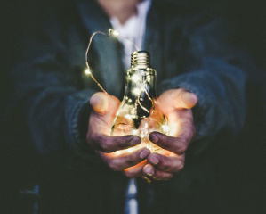 Person holding glowing light bulb in hands.