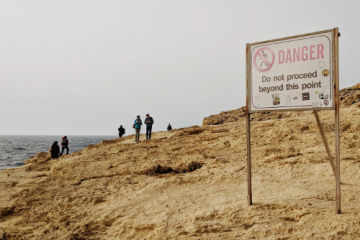 People on cliff with sign of danger