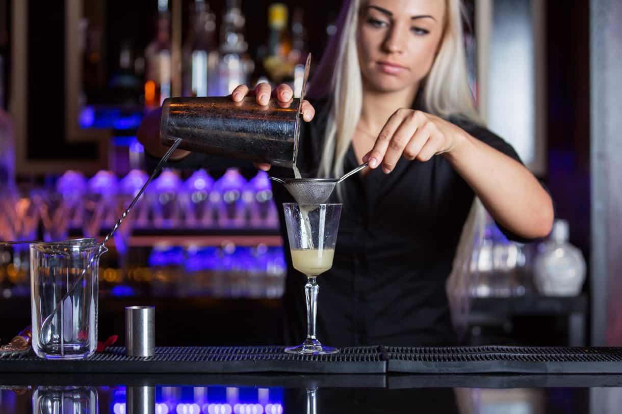 bartender filtering the cocktail drink