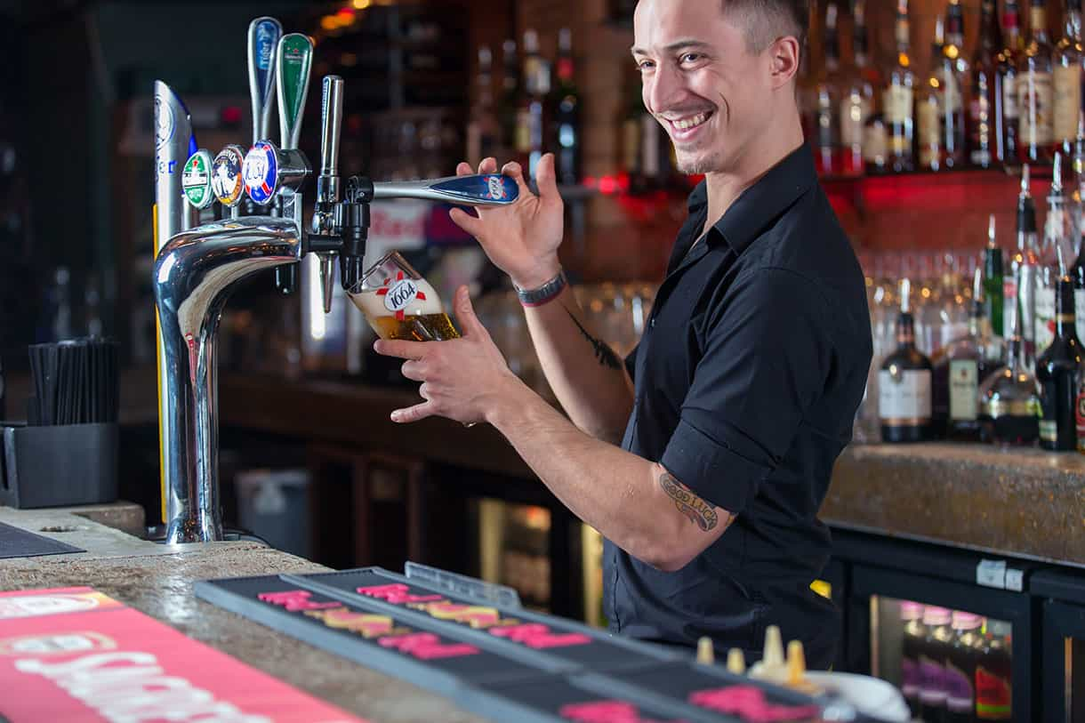 bartender pouring a pint of beer