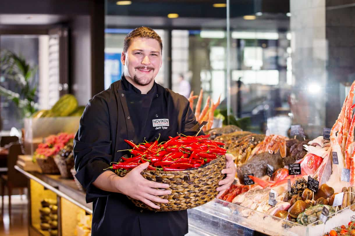 portrait of a smiling chef holding a basket of red chillies