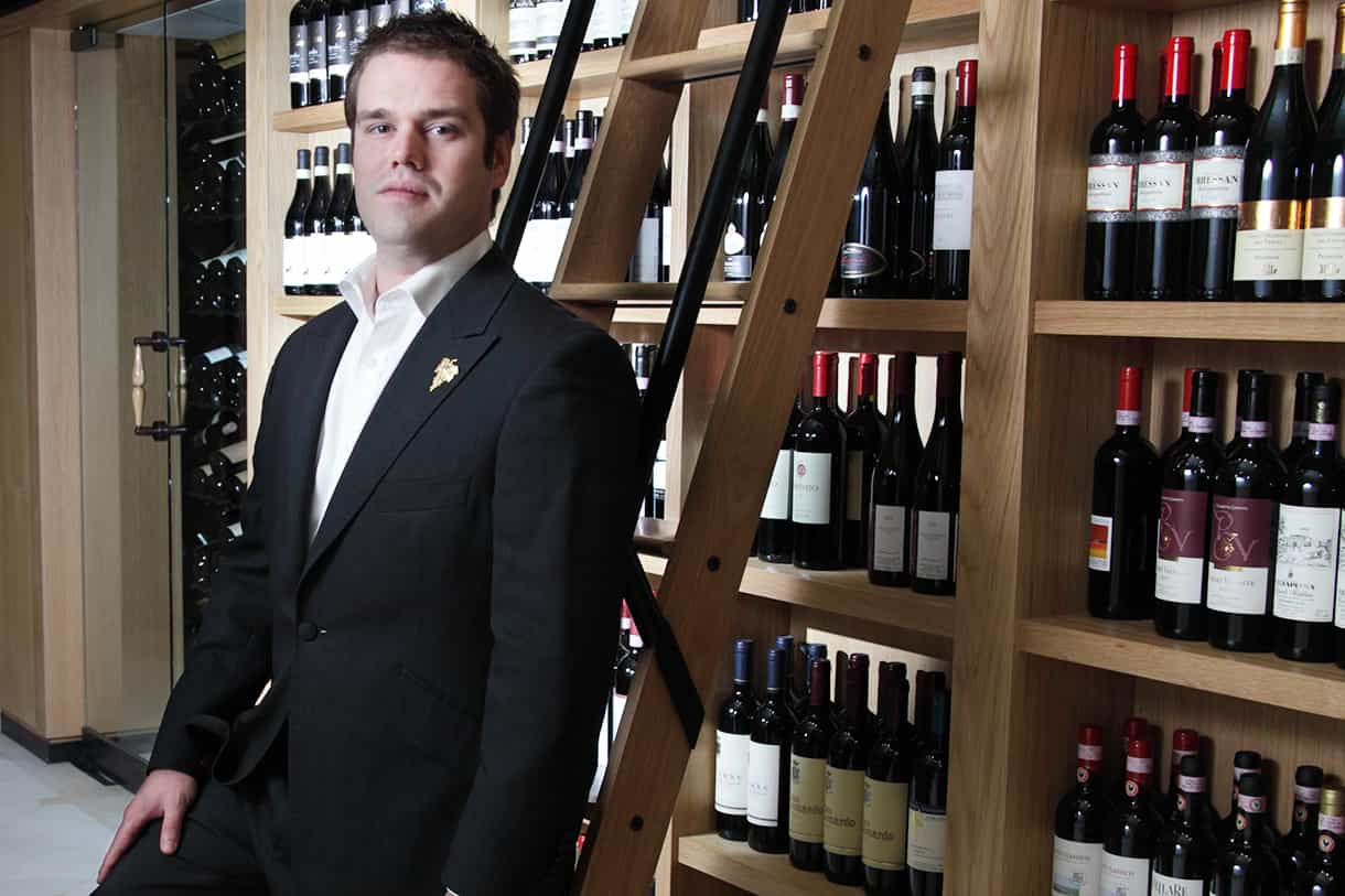 portrait of a sommelier against a display of wine bottles