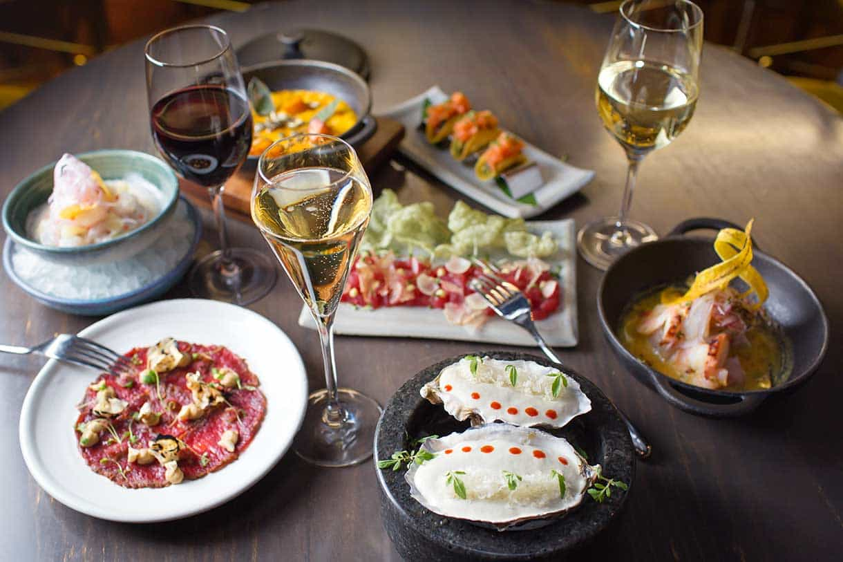 various dishes such as beef carpaccio, oysters, ceviche with glasses of wine and champagne