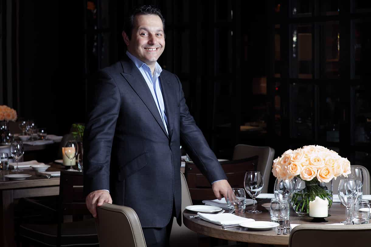 portrait of man in a suit next to a restaurant table set-up