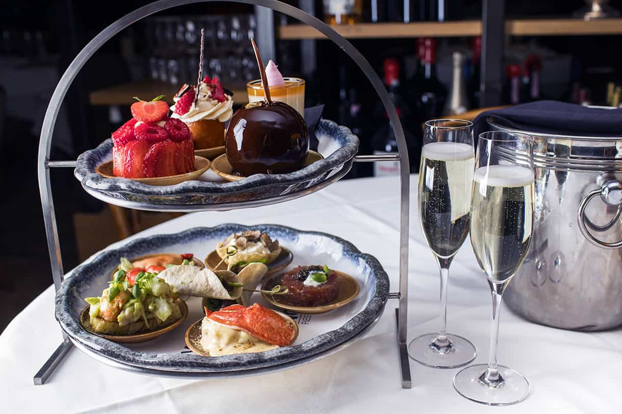 afternoon tea cakes and sandwiches with 2 glasses of champagne