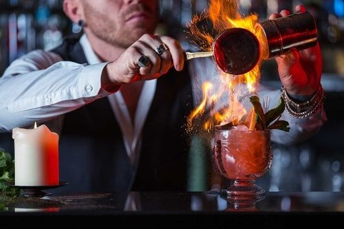 bartender making a flambe cocktail
