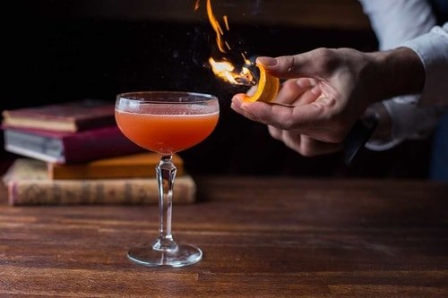 bartender giving flavour to a cocktail with an orange peel