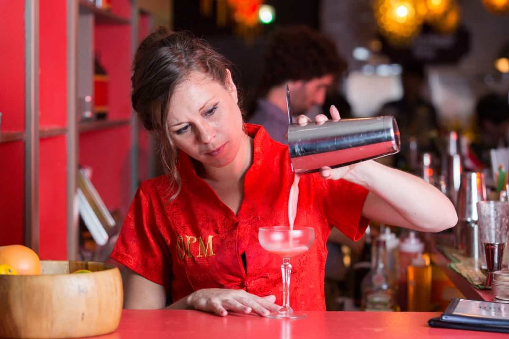 bartender pouring the cocktail drink in a glass
