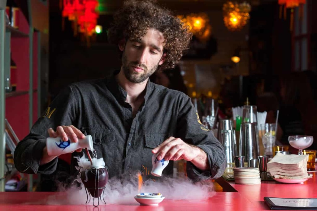 bartender pouring a drink in a cocktail