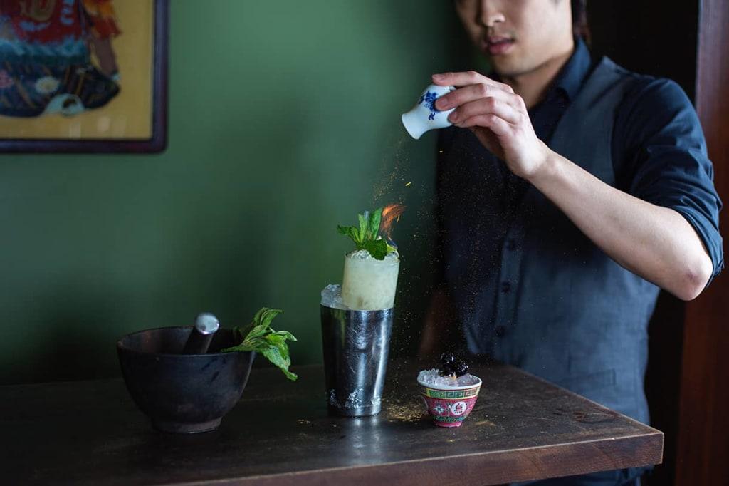 bartender sprinkling cinnamon on a cocktail drink garnished with mint