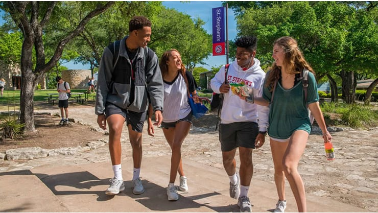 Four students walking and laughing on campus at St. Stephens Episcopal School