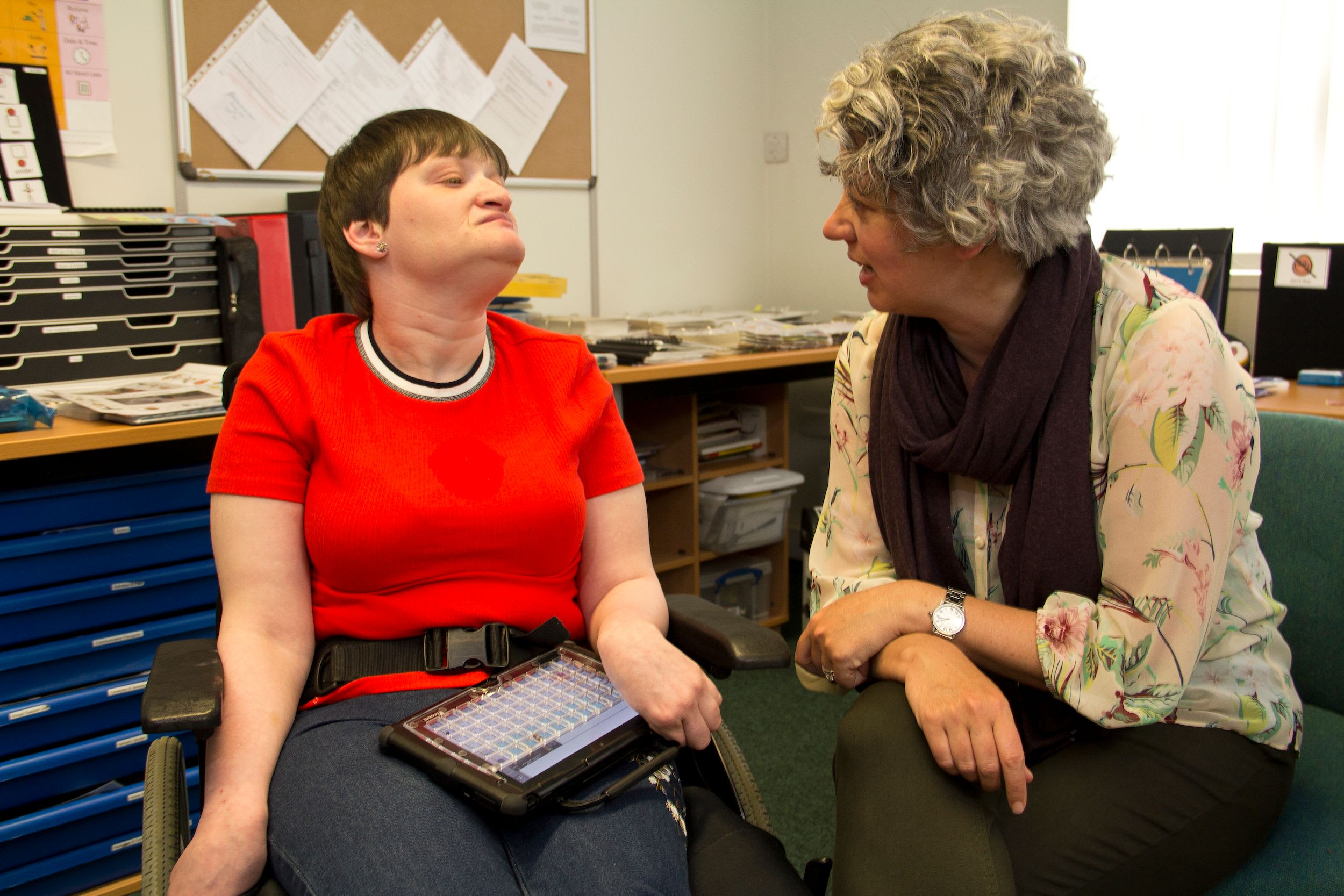 Two people talking, one using AAC