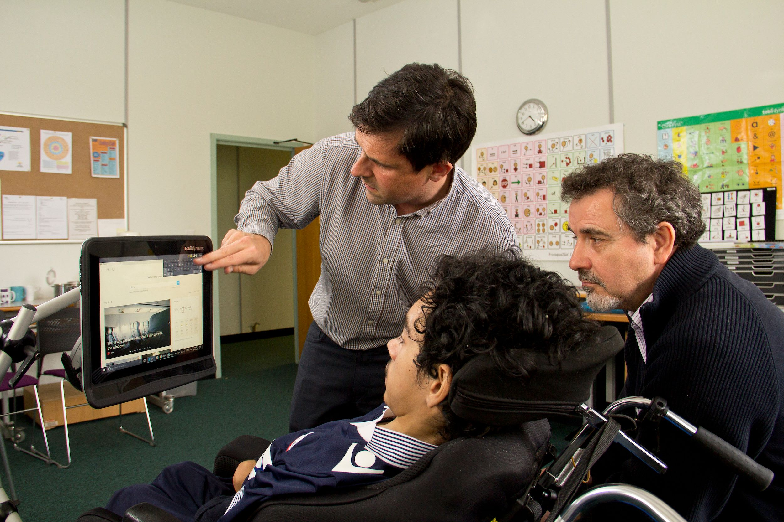 An Ace Centre staff member showing a client how to use their device