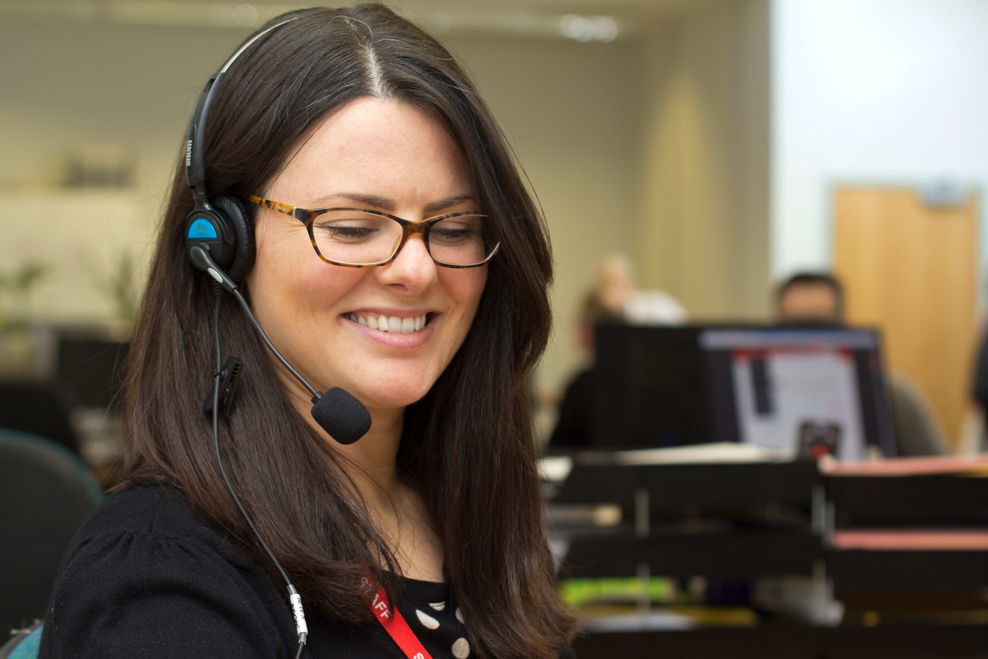 A woman smiling whilst taking a call on a headset