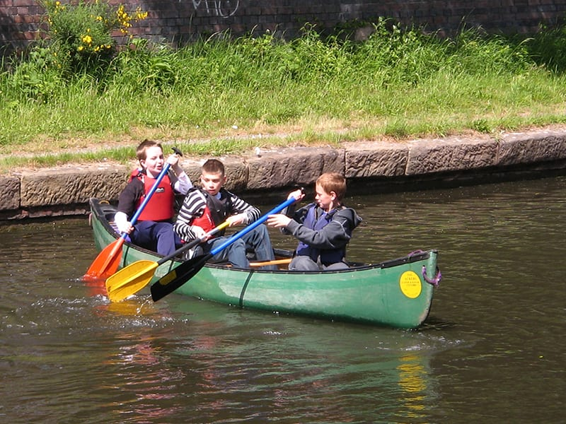 3 young boys canoeing