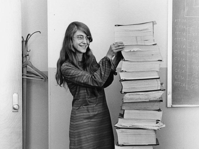 Margaret Hamilton stands next to a stack of program listings from the Apollo Guidance Computer in a photograph taken in 1969 (Wikimedia Commons)